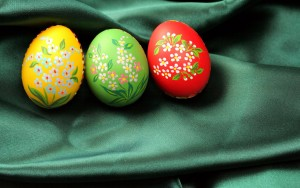 Three Easter eggs (red, yellow and green) lying on dark green satin fabric - textile.